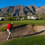 Skyline Country Club - Chipping out of a bunker in front of golf homes and the mountains in the Tucson Arizona golf community